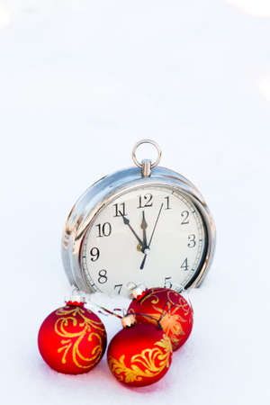 Three red christmas balls and clock on a snow. New Year greeting card concept. Copy-space Stock Photo