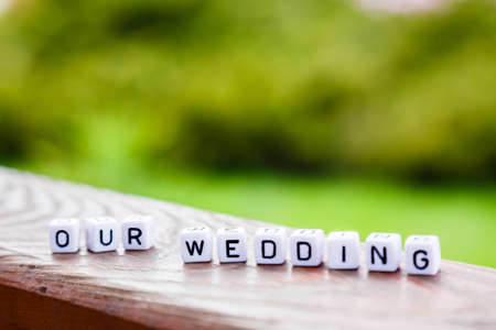 Word of the cubes our wedding on a wooden stand on green background Stock Photo