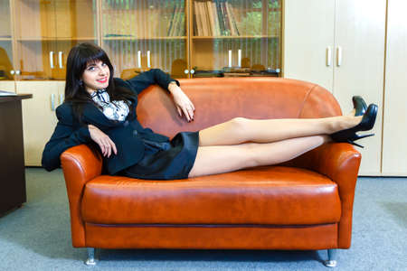 Young beautiful woman relaxing on a sofa in the office