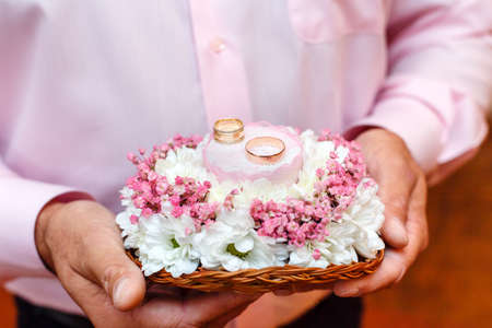 Groom holding flowers bouquet with two wedding rings Stock Photo