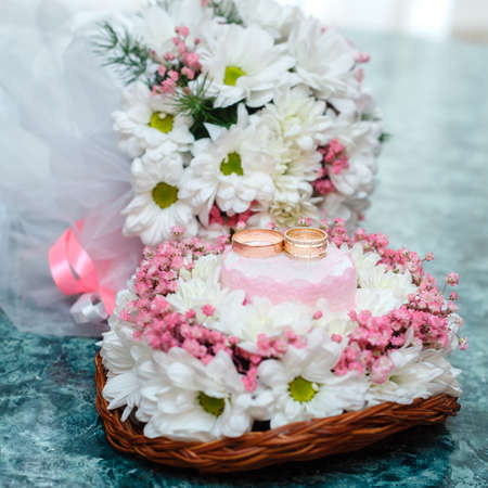 basketry: Two gold wedding rings on Beautiful white and pink bouquet in rustic basketry.. Close up. Stock Photo