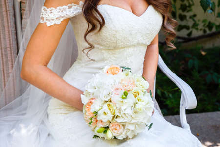 Sitting Bride holding a beautiful wedding bouquet of roses and eustoma. Stock Photo