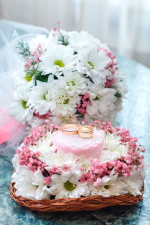 trillium: Two gold wedding rings on Beautiful white and pink bouquet in rustic basketry.. Close up. Stock Photo