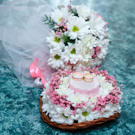 Two gold wedding rings on Beautiful white and pink bouquet in rustic basketry.. Close up. Stock Photo
