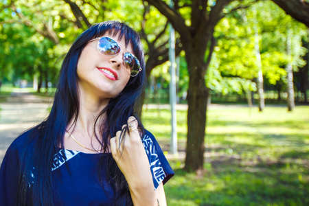 Portrait of beautiful young brunette girl in sunglasses with long hair walking along the alley in the park