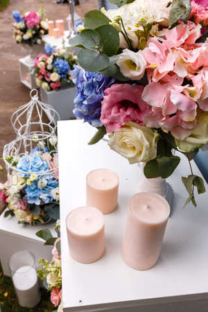 outoors: Wedding ceremony decorations bouquets of flowers eustoma and roses, candles in restaurant outdoors. Stock Photo