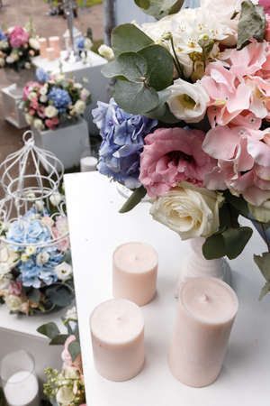 formal dinner party: Wedding ceremony decorations bouquets of roses and eustoma, candles in restaurant outdoors. Stock Photo