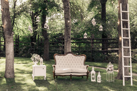 outoors: Wedding ceremony decorations bouquets of roses, sofa, staircase in a park outdoors.