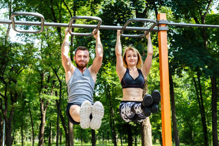 Young sportive woman and bearded man doing pull-ups exercises on crossbar in a parrk at summer day. Stock Photo