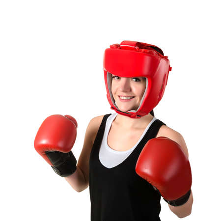 young brunette woman in red boxing gloves and helmet making impact, looking at camera. Isolated on white background.