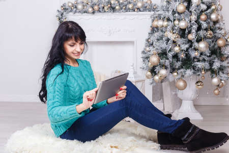 Happy caucasian woman with long brunette hair sitting indoors in christmas decoration using a white tablet PC.