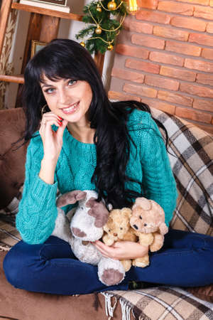 living room sofa: Caucasian smiling young woman sitting on sofa in christmas decorated interior, holding a bears toys. Looking at camera.