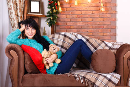 living room sofa: Cute smiling hispanic girl sitting on sofa in christmas decorated interior, holding a bears toys. Looking at camera. Stock Photo