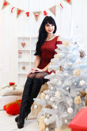 Attractive young brunette woman in red dress sitting indoors in a christmas decorated interior. Looking at camera.  Stock Photo