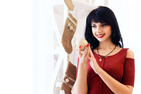 Happy young brunette woman in red dress holding a christmas ball in a New Year decorated room. Preparation for the celebration of Christmas