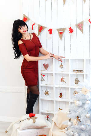 Beautiful  young brunette woman in red dress sitanding in a christmas decorated interior. Looking at camera. Stock Photo