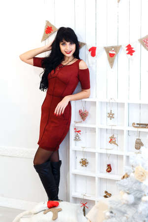 Beautiful  young brunette girl in red dress sitanding in a christmas decorated interior. Looking at camera.