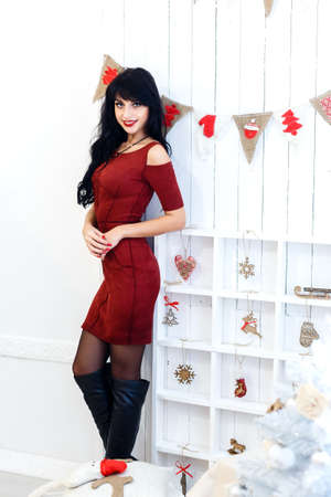 good color: Happy young brunette woman in red dress sitanding in a christmas decorated interior. Looking at camera.