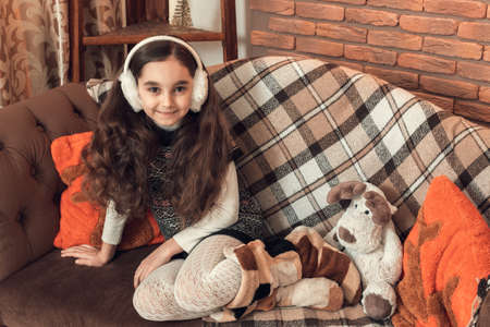 Pretty little brunette girl with long hair sitting on a sofa at christmas decorated room. Celebrating xmas at home. Smiling, looking at camera.