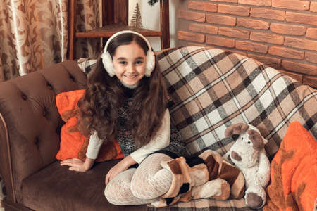 Happy little brunette girl with long hair sitting on a sofa at christmas decorated room. Celebrating xmas at home. Smiling, looking at camera. Banco de Imagens