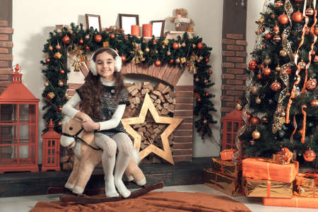 Cute little brunette girl with long hair sitting on a toy horse at christmas decorated room. Celebrating xmas at home. Smiling, looking at camera.