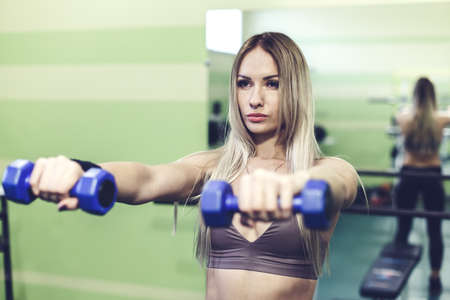 Young blonde woman doing exercises with dumbbells in a GYM. Healthy lifestyle concept.