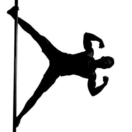 silhouette of young athletic man doing strength exercises on a pylon. Pole Dance