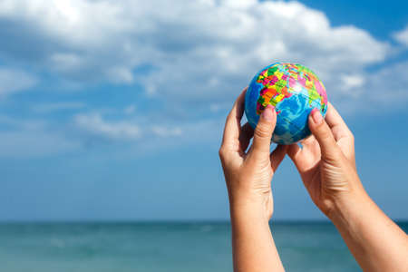Woman holding globe of the Earth on a background of the sea. Concept ecology, peace,, save the planet Earth.
