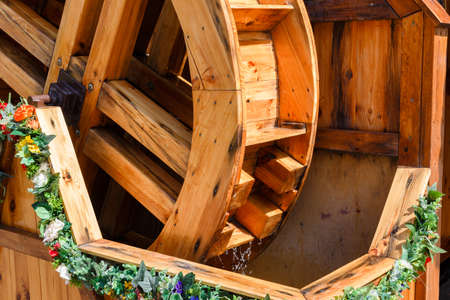 Beautiful wooden water mill decorated with flowers.