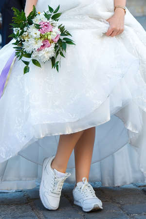 Bride with a wedding bouquet dressed in a white dress showing sneakers on her legs.