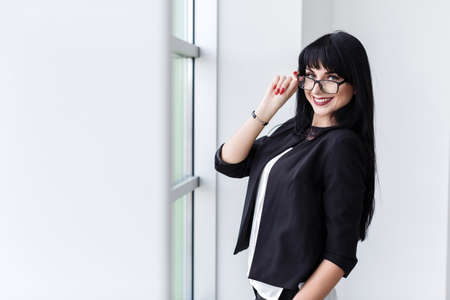 Portrait of young beautiful happy woman with glasses standing near the window, looking at camera smiling.