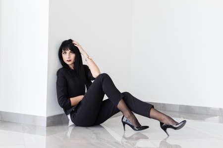 Joven hermosa mujer morena seria vestida con un traje negro sentada en el piso de una oficina con paredes blancas.