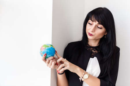 Young Beautiful smiling brunette woman dressed in a black business suit holding a globe of the planet Earth, skeptical looks at the globe. Travel concept.