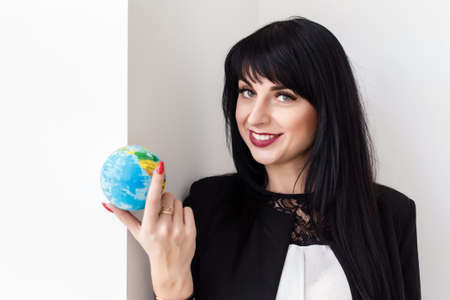 Young Beautiful smiling brunette woman dressed in a black business suit holding a globe of the planet Earth. Travel concept.