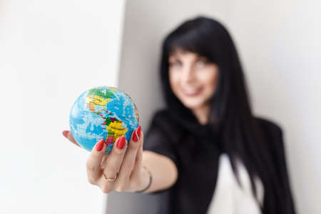 Young Beautiful smiling brunette woman dressed in a black business suit holding a globe of the planet Earth. Travel concept. Shallow depth of field. 写真素材
