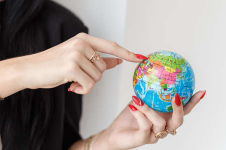 Young woman holding a globe of the planet Earth, Showing by finger to Ukraine close-up. Travel concept. 写真素材
