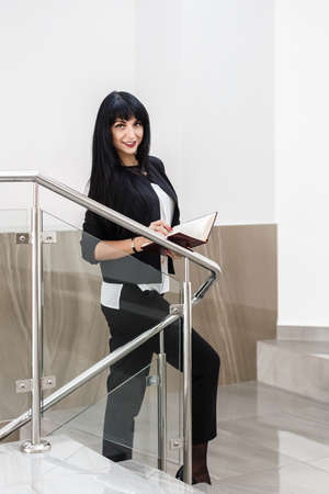 Young Attractive happy brunette woman dressed in a black business suit holding a note book, standing in a office, smiling, looking at camera. 写真素材
