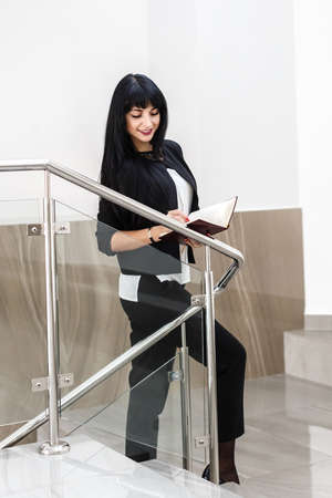 Young Pretty Smiling brunette woman dressed in a black business suit working with a notebook, standing in a office.
