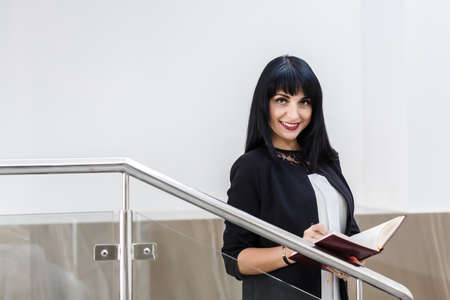 Portrait of Young Attractive happy brunette woman dressed in a black business suit working with a notebook, standing in a office, smiling, looking at camera.