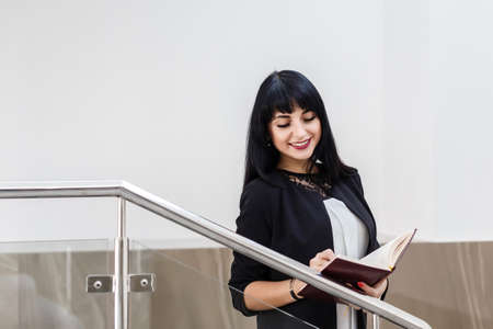 Portrait of Young Beautiful happy brunette woman dressed in a black business suit working with a notebook, standing in a office, smiling. 写真素材