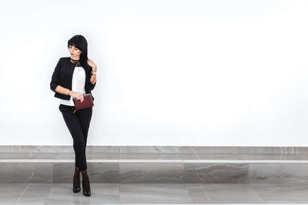 Young attractive serious brunette woman with a note book dressed in a black business suit  standing against the white wall in a office. Copy space. 写真素材