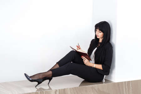 Young Attractive serious brunette woman dressed in a black business suit sitting on a floor in a office, reading in a notebook. Isolated on white background.