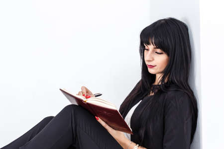 Young Beautiful serious brunette woman dressed in a black business suit sitting on a floor in a office, writes in a notebook, Isolated on white background.