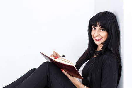Young Beautiful happy brunette woman holding a notebook dressed in a black business suit sitting on a floor in a office, smiling, looking at camera. Isolated on white background.