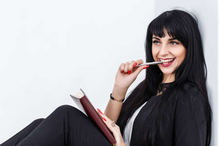 Young Beautiful happy brunette woman holding a notebook dressed in a black business suit sitting on a floor in a office, smiling, Isolated on white background.