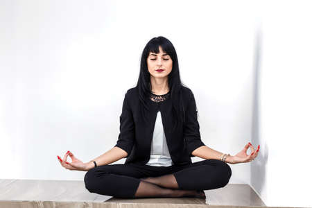 Beautiful young serious woman dressed in a black business suit sitting in lotus position on a floor in a office, closed her eyes.