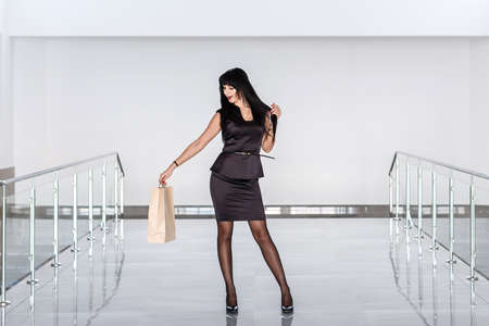Young Beautiful happy brunette woman dressed in a black business suit holding paper shopping bag, walking on a mall.
