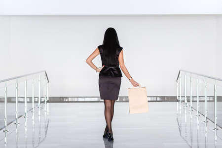 Young Attractive brunette woman dressed in a black business suit holding paper shopping bag, walking on a mall. Back to camera.