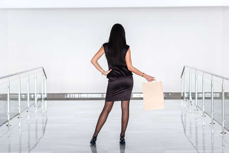 Young Attractive brunette woman dressed in a black business suit holding paper shopping bag, walking on a mall. Back to the camera.