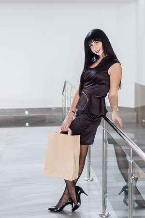 Young Attractive smiling brunette woman dressed in a black business suit holding paper shopping bag, walking on a mall. Looking at camera.